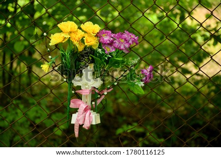 Close up on a plastic Christian cross attached to a metal fence by means of a pink ribbon or cloth with two handfuls of colorful flowers attached to it spotted on a sunny summer day in Poland