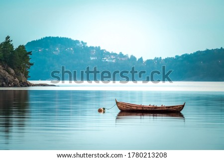 Small wooden boat in the middle of a lake, Lonely wooden boat in the water, isolated wooden boat, Top view of a white small wooden boat floating in the middle of a lake #1780213208