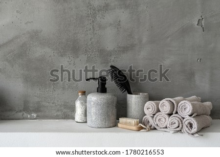Close up of bottle with soap dispenser, hairbrush, bath salt, clean and fresh rolled towels near soft nail brush on shelf in bathroom against grey copy space wall on background #1780216553