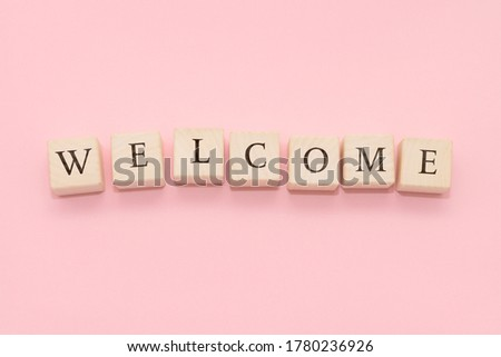 The word WELCOME is made of wooden cubes on a yellow background.
