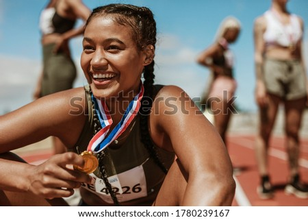 Female runner with a gold medal sitting on track. Running race winner sitting on track with athletes in background. Royalty-Free Stock Photo #1780239167