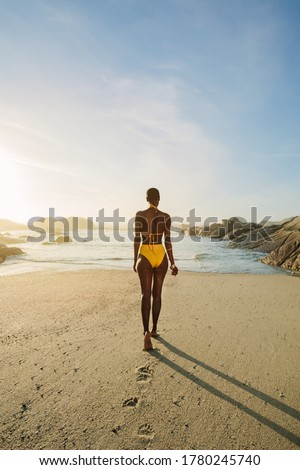 Rear view of a african woman wearing yellow bikini walking into the sea. Woman walking towards sea in swimwear on a summer day.