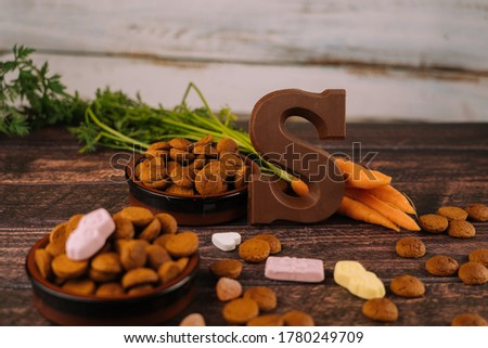 Dutch holiday Sinterklaas. Background with traditional food - pepernoten, chocolate letter, sweets strooigoed and carrots for horse. Concept for children party in Saint Nicolas day five december Royalty-Free Stock Photo #1780249709