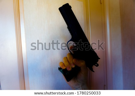 A male hand with the finger on the trigger holds a fake but realistic gun (children's toy pistol), featuring a metal-look black plastic body, and points the weapon upwards, towards the ceiling #1780250033