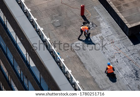 Birds eye view of a roof construction site. Professional bitumen waterproofing on a flat building. Royalty-Free Stock Photo #1780251716