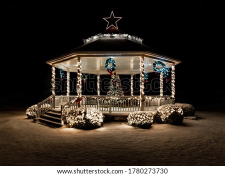 Gazebo decorated for Christmas with tree, lights and snow
