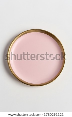 New luxury plate view from above on a isolated white background. Top view. Porcelain pink saucer with gold ring. Trendy Coral tones. Flat lay view. #1780291121