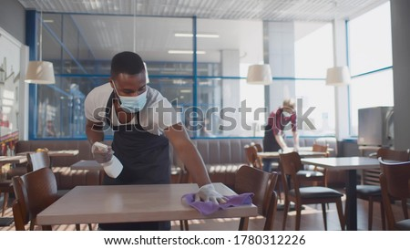African male worker cleaning table with disinfectant in restaurant during coronavirus outbreak. Waiter in protective mask and gloves disinfecting table with spray and cloth #1780312226
