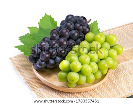 Sweet Green grape and Black grape in Bamboo basket isolated on white background, Shine Muscat Grape and Kyoho Grape with leaves isolated on white  #1780357451
