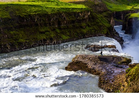 """Tourist with a photo bag takes pictures of a bubbling waterfall. Gullfoss """"Golden Falls"""" - the waterfall fed by thawed glacial water. Iceland. The concept of extreme and photo tourism"""