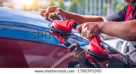 Mechanic car service changing windshield  mirror by used technology replacing new windscreen or windshield of a car in auto service garage. Royalty-Free Stock Photo #1780391090