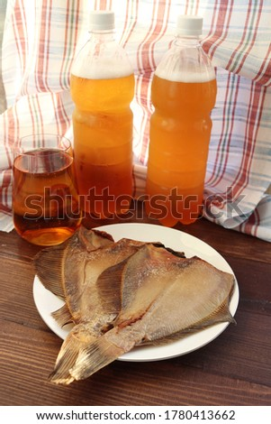 Appetizing and bright still life with draft light beer and smoked flounder. An ideal snack for beer drinks.