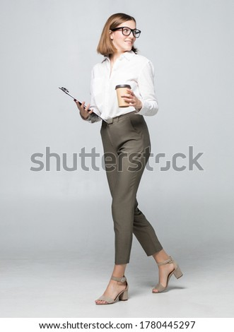 Young beautiful woman drinking coffee holding clipboard isolated over white wall background