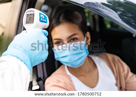 Medical staff with PPE Take Temperature for fever to asian woman before coronavirus covid-19 test at drive thru station in hospital. New normal healthcare drive thru service and medical concept. #1780500752