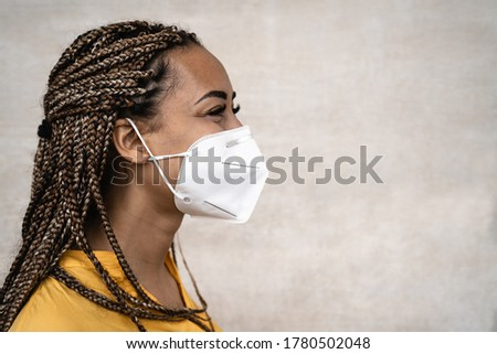 African woman with braids wearing face medical mask - Young girl using facemask for preventing and stop corona virus spread - Healthcare medical and youth millennial people concept  Royalty-Free Stock Photo #1780502048