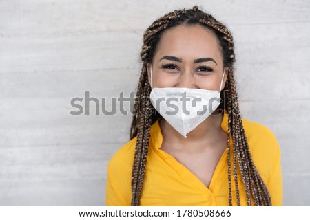 Young woman with braids smiling in front of the camera while wearing face mask during coronavirus outbreak - Covid 19 spread prevention and young people lifestyle concept #1780508666