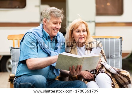 Mature woman with her husband looking through family photo album near trailer at campsite