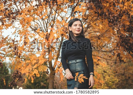fall scene beautiful autumn portrait of attractive young woman in park against tree with yellow orange leaves holding a tender twig and looking away in the distance