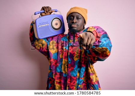 Young african american man listening to music holding portable vintage retro radio pointing with finger to the camera and to you, hand sign, positive and confident gesture from the front