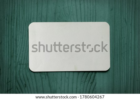 White business card template on a green wooden background. White paper on a green wood texture.
