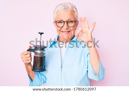 Senior beautiful woman with blue eyes and grey hair holding french coffee maker doing ok sign with fingers, smiling friendly gesturing excellent symbol