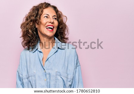 Middle age beautiful woman wearing casual denim shirt standing over pink background looking away to side with smile on face, natural expression. Laughing confident. Royalty-Free Stock Photo #1780652810