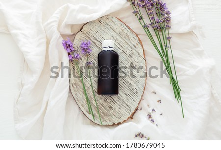Lavender flowers with lavender essential oil bottle on white wooden rustic board and fabric. Aromatherapy treatment, natural organic spa cosmetics, homeopathy apothecary lavender herb. Flatlay #1780679045