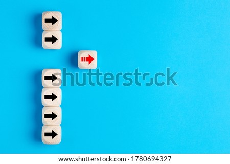 Wooden blocks with arrows with one moving forward and standing out from the crowd. Concept of competitive advantage in business startup.  Royalty-Free Stock Photo #1780694327