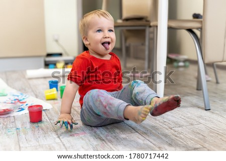 Adorable cute caucasian little blond naughty toddler boy enjoy having fun painting with brush and palm at home indoors . Cheerful happy kid smiling drawing masterpiece art picture. Messy dirty room