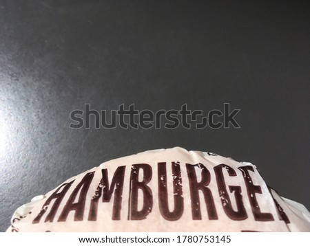 A picture of a hamburger wrapped in paper with the message of a hamburger. Placed on the table There is a slight shadow and reflection. With text written to compose the image, decorated with ACDSee pr