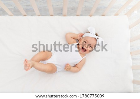 baby girl 6 months old lies in a crib in the nursery with white clothes on her back and laughs, looks at the camera, baby's morning, baby products concept #1780775009