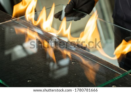 Glazier cuts safety glass, VSG (Very Safe Glass) The fire burns through the foil connecting the panes, A specialized technique of cutting laminated glass Royalty-Free Stock Photo #1780781666