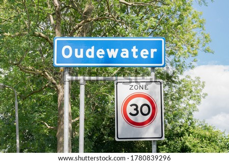 """Place name sign of Oudewater, a town in the western part of The Netherlands. Sign with """"Zone 30"""" indicates the speed limit in the specific area."""