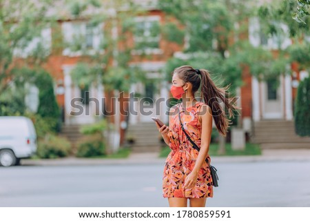 COVID-19 girl walking in city street wearing face mask. Mandatory wear Asian woman commuting using mobile phone. protection as prevention for coronavirus outside in city park summer. Corona virus. #1780859591