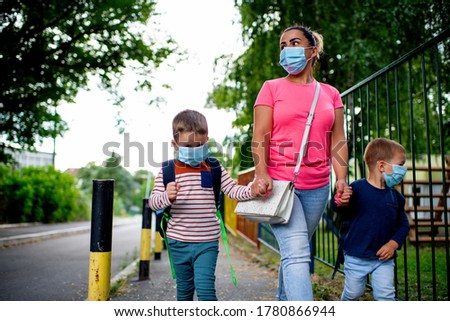 Mother and children going to preschool during corona virus. Surgical mask for illness prevention. Royalty-Free Stock Photo #1780866944