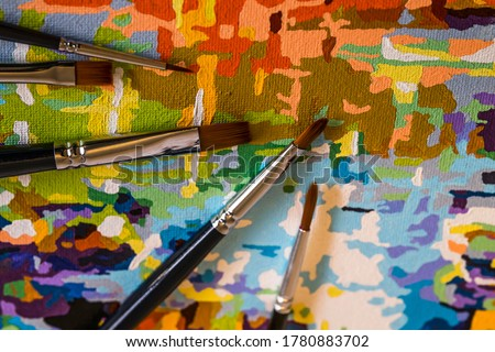 Art brushes and painting. Brush strokes of bright colors close-up. A fragment of the picture. Acrylic paints. Macro photo. Painter