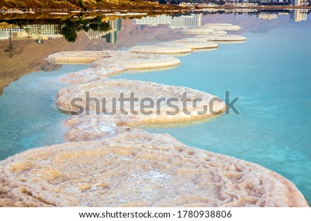 Misty winter day over the Dead Sea. Evaporated salt protrudes above water. The sky merges with the sea on the horizon. Israel. The concept of active and photo tourism