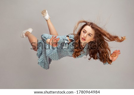 Beautiful girl levitating in mid-air, falling down and her hair messed up soaring from wind, model flying hovering with dreamy peaceful expression. indoor studio shot isolated on gray background Royalty-Free Stock Photo #1780964984