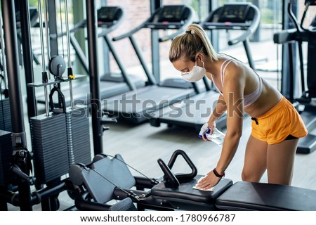 Athletic woman with face mask cleaning exercise machine with disinfectant while exercising in a gym during coronavirus epidemic.  #1780966787