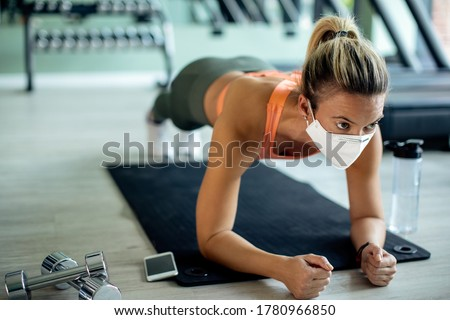 Female athlete exercising strength in plank pose while wearing protective face mask at health club.  #1780966850