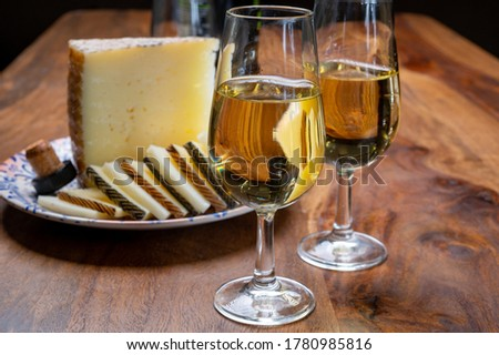Spanish fino dry sherry wine from Andalusia and pieces of different sheep hard manchego cheeses made in La Mancha, Spain. Wine and cheese pairing Royalty-Free Stock Photo #1780985816