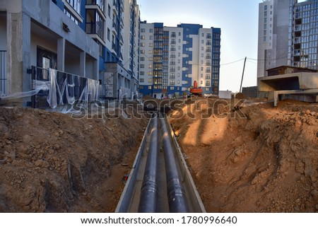 Laying heating pipes in a trench at construction site. Install underground storm systems of water main and sanitary sewer. Cold and hot water, heating and heating system of apartments in the house Royalty-Free Stock Photo #1780996640