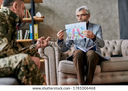 Mature psychologist holding picture with ink stain, Rorschach Inkblot in front of military man during therapy. Soldier suffering from depression, psychological trauma. PTSD concept. Focus on picture