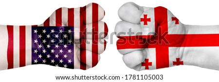 The concept of the struggle of peoples. Two hands are clenched into fists and are located opposite each other. Hands painted in the colors of the flags of the countries. Georgia vs USA