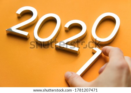Close-up of metal numbers 2021 and hand on orange background. change year 2020 to 2021 #1781207471