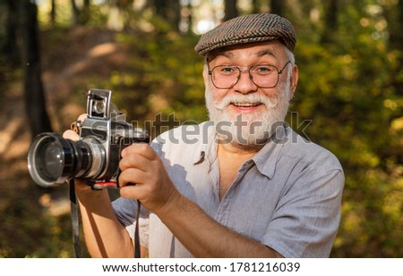 Vintage camera. Old man shoot nature. Professional photographer. Make perfect frame. Landscape nature photo. Old photographer filming. Manual settings. Pension hobby. Experienced photographer.