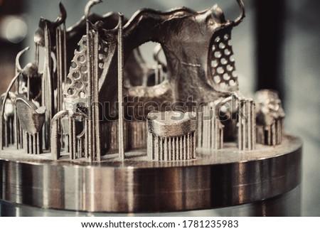 Object printed on metal 3d printer close-up. Object printed in laser sintering machine. Modern 3D printer printing from metal powder. Concept progressive additive DMLS, SLM, SLS 3d printing technology #1781235983