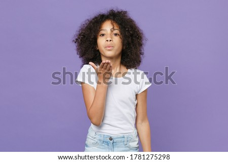 Pretty little african american kid girl 12-13 years old in white t-shirt isolated on violet wall background studio portrait. Childhood lifestyle concept. Mock up copy space. Blowing sending air kiss