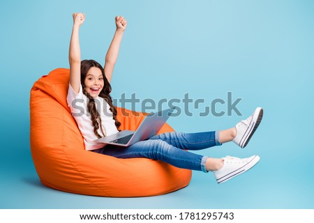 Portrait of nice attractive cheerful cheery excited glad wavy-haired girl sitting in chair using laptop celebrating win isolated on bright vivid shine vibrant blue teal turquoise color background #1781295743
