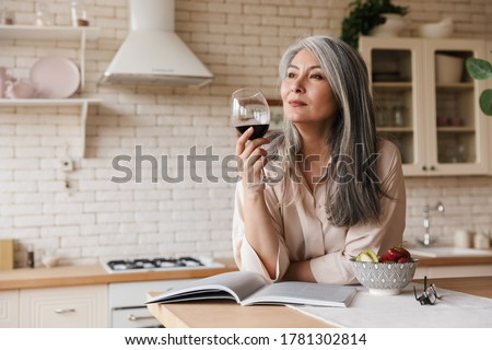 Picture of mature amazing pretty woman sitting at the kitchen indoors at home drinking wine